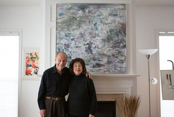 The painter Nelly Toll, a Holocaust survivor, and her husband, Herb Toll, in front of two of her recent paintings in their home in Vorhees, N.J. Credit Jessica Kourkounis for The New York Times
