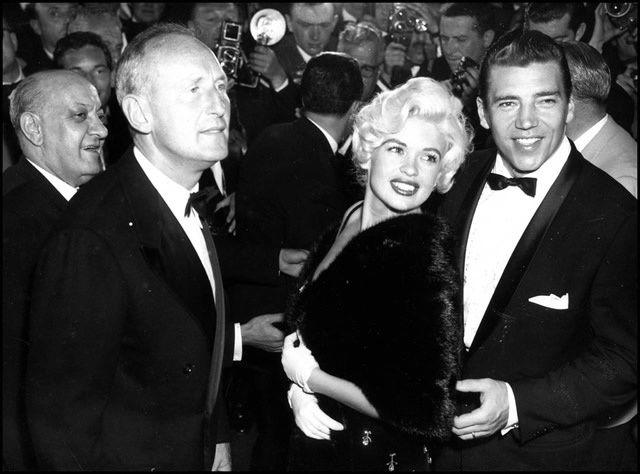 """Jayne Mansfield, lors d'une tournée. Elle ne refusait jamais une interview et venait souvent en Europe. Voici la starlette, avec son mari Mickey et un compagnon inattendu : Bourvil. Lui a -t-il dit que sans """"décolleté"""" profond, ça """"marcherait beaucoup moins bien"""" ?!"""