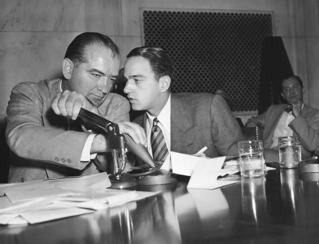 Sen. Joseph McCarthy covers the microphones with his hands while having a whispered discussion with Roy Cohn, his chief counsel, during a committee hearing on April 26, 1954, in Washington.   AP Photo