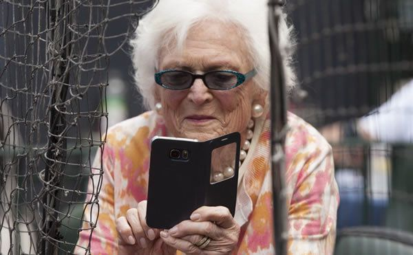 Former first lady Barbara Bush takes photos with her cellphone before a Houston Astros game in Houston in this May 3, 2015, photo. The Associated Press