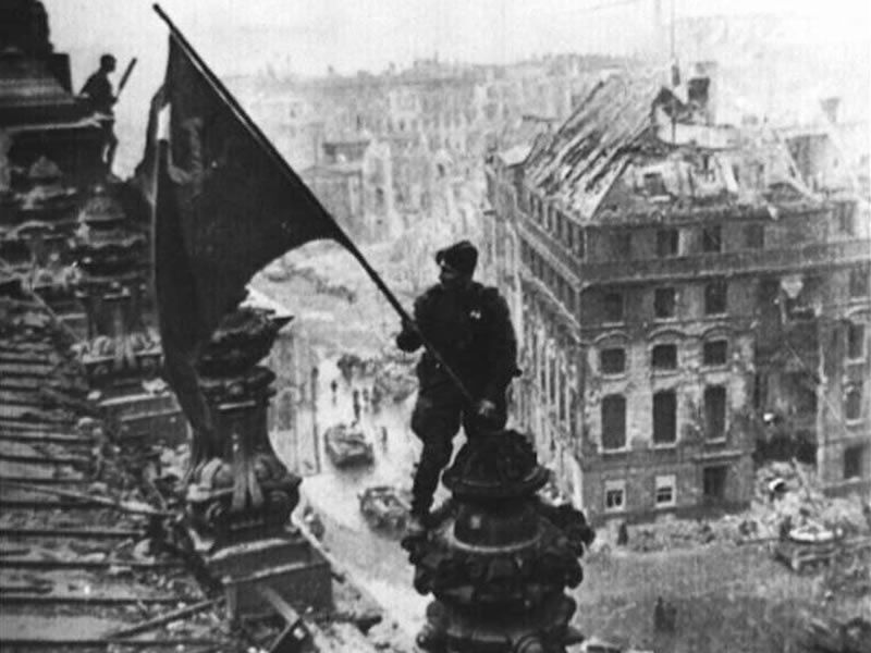 A Soviet soldier raises his nation's flag over the Reichstag, the German parliament building in Berlin, on April 30, 1945, after Germany surrendered, ending World War II.(AP Photo/ITAR-TASS)