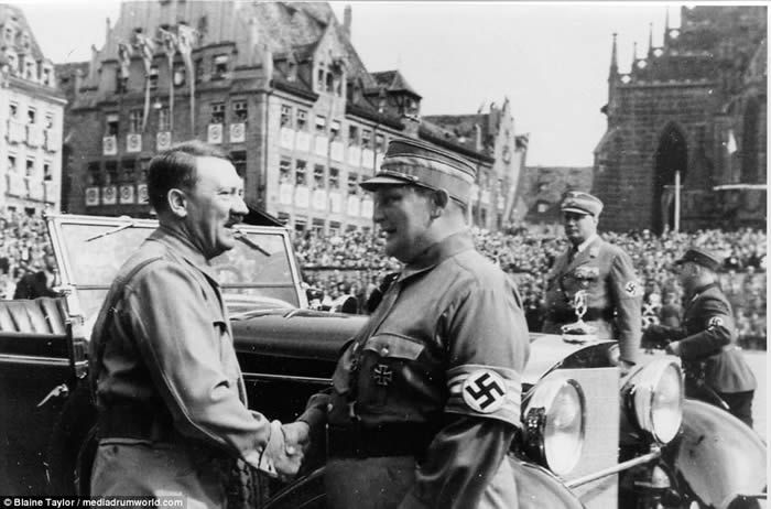 The Führer's friend: Smiling Hitler is pictured at the christening of his close confidant Hermann Goering's daughter in new book illustrating the Nazis before the war broke out