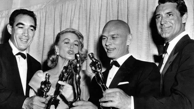 Dorothy Malone au côté d'Anthony Quinn, Yul Brynner et Cary Grant lors de la cérémonie des Oscars le 27 mars 1957. Rue des Archives/©Rue des Archives/BCA