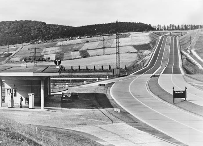 In this photograph snapped during the 1930s, a section of the modern Autobahn stretches into the distance across the German countryside. Note the service station at left.