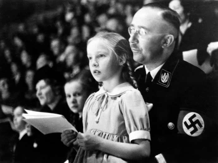 In this March 6, 1938 file photo SS Chief Heinrich Himmler with his daughter Gudrun on his lap watch an indoor sports display in Berlin