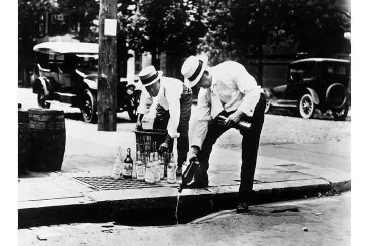 Two men pour alcohol down a drain during prohibition in the United States, c1920. (Hulton Archive/Getty Images)