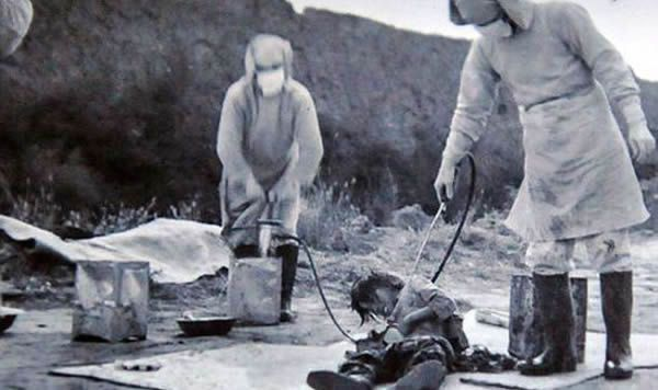 Soldiers spray a Chinese civilian with chemicals