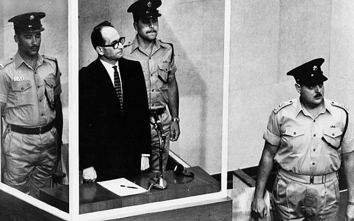 This 1961 file photo shows Adolf Eichmann standing in his glass cage in the Jerusalem courtroom where he was tried and convicted of war crimes committed during World War II. (AP Photo,b/w file)