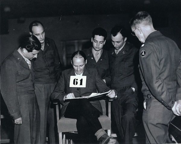 Victor Zoller (defendant 61) examines documents during the Mauthausen war crimes trial. From left to right are the interpretter, Lt. Col. Ernst Oeding (defense attorney), Victor Zoller, Lt. Paul Guth (interrogator), William Denson (chief prosecutor) and Lt. Robert Wilson.