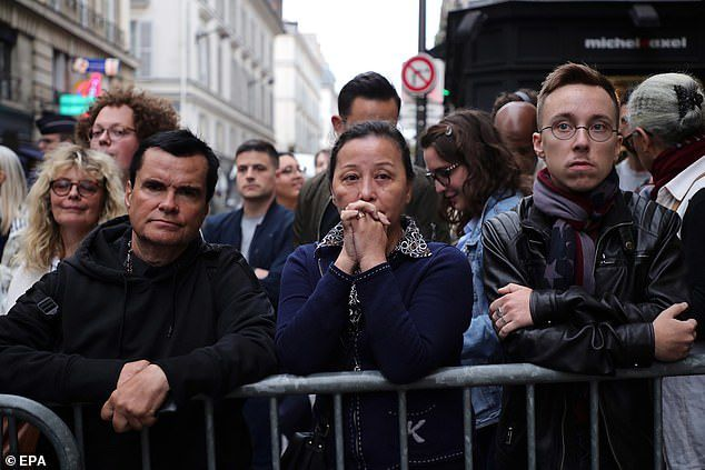 Emotional supporters gather near the apartment of the late French former president Jacques Chirac yesterday