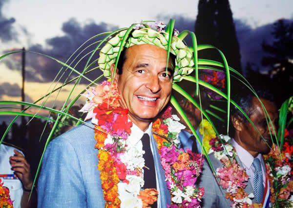 Le Premier ministre Jacques Chirac, coiffé d'un chapeau traditionnel, sourit le 29 août 1986, lors de son arrivée à Nouméa. REMY MOYEN / AFP