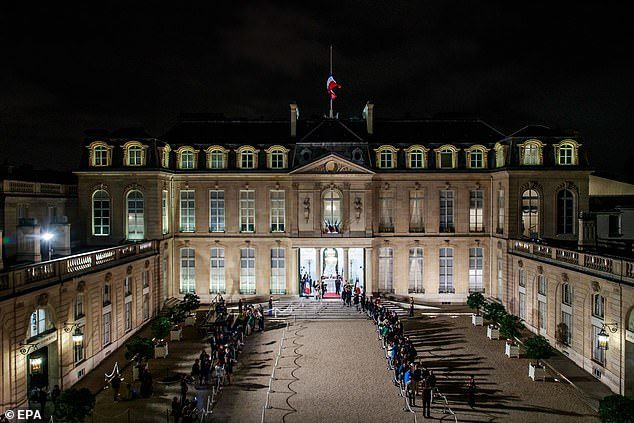 People are seen queuing at the Elysee Palace in Paris to offer their condolences