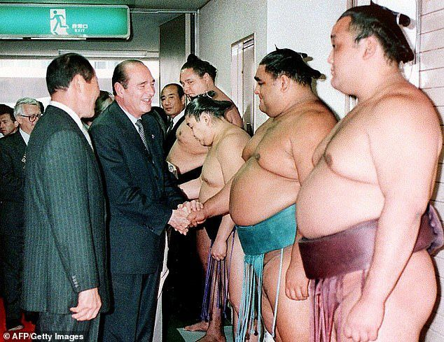 Chirac is greeted by Sumo wrestlers on a visit to Japan in November 1996 during his first term as President of France