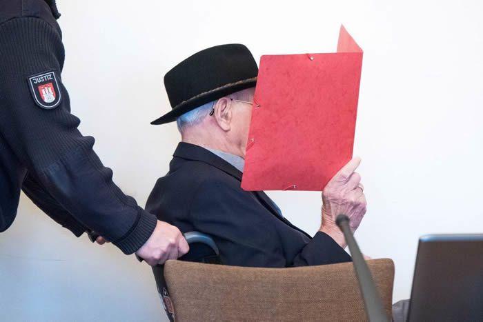 Da den 93-årige tidligere SS-vagt Bruno Dey mødte op i retten i Hamburg torsdag, sad han i kørestol og var iført hat og solbriller. Han dækkede sit ansigt med en rød folder. (Foto: Daniel Bockwoldt/Ritzau Scanpix)
