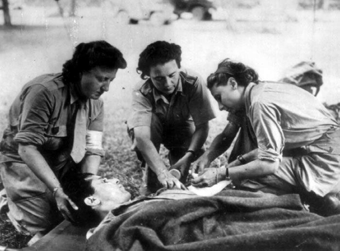 image d'illustration- Trois Rochambelles de la Division Leclerc soignent un blessé sur un brancard. / © PhotosNormandie via flickr