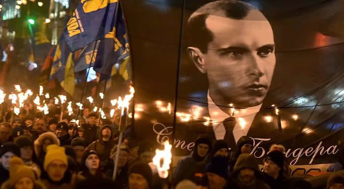 """People carry torches during the """"March of Honor, Dignity and Freedom"""" in Kiev on January 1, 2020 to mark the 111th anniversary of the birth of Ukrainian politician Stepan Bandera (1909-1959)."""