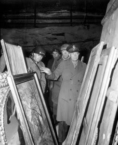 Gen. Dwight D. Eisenhower, Supreme Allied Commander, accompanied by Gen. Omar N. Bradley, and Lt. Gen. George S. Patton, Jr., sift through art stolen by Germans and hidden in salt mines. Courtesy Wikimedia Commons.