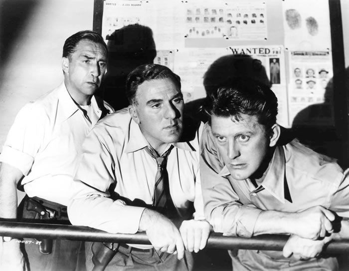 "From left, Horace McMahon, William Bendix and Mr. Douglas in the 1951 film ""Detective Story."" Mr. Douglas was praised for his portrayal of an overzealous New York detective who invites his own destruction.Credit...Paramount Pictures, via Associated Press"