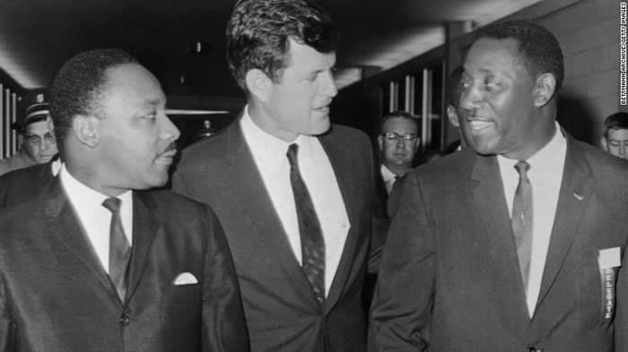 In this undated image, Sen. Ted Kennedy talks with the Rev. Martin Luther King Jr., left, and Charles Evers, then the Mississippi NAACP field director, in Jackson.