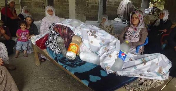 Une famille veille un corps qui ne peut êtrer évacué, protégé par des bouteilles d'eau froide