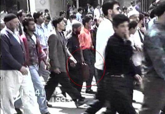 Les émeutiers se dirigent vers l'hôtel Madımak. L'un d'eux porte un bidon d'essence (cercle rouge). Cette photo fait partie de la série qui a servi pour l'enquête de la Commission parlementaire sur le drame