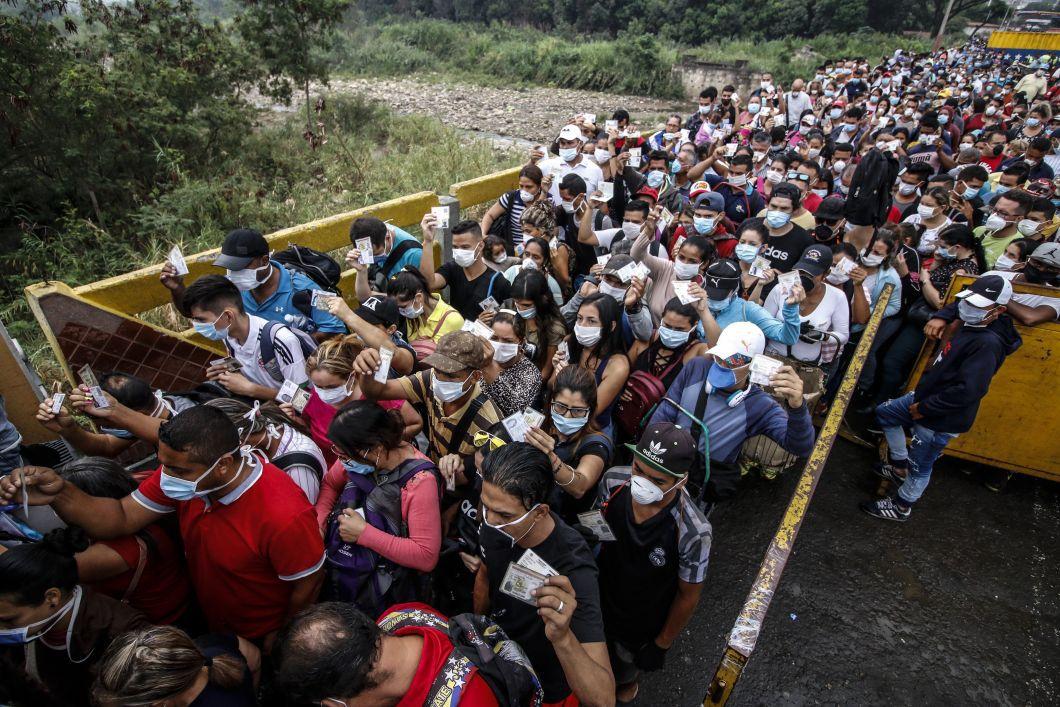 Schneyder Mendoza / AFP - Des personnes venant du Venezuela avec des masques protecteurs par mesure de précaution pour éviter de contracter le nouveau coronavirus Covid-19 montrent leurs documents à la frontière au pont international Simon Bolivar, à Cucuta, en Colombie, le 12 mars.