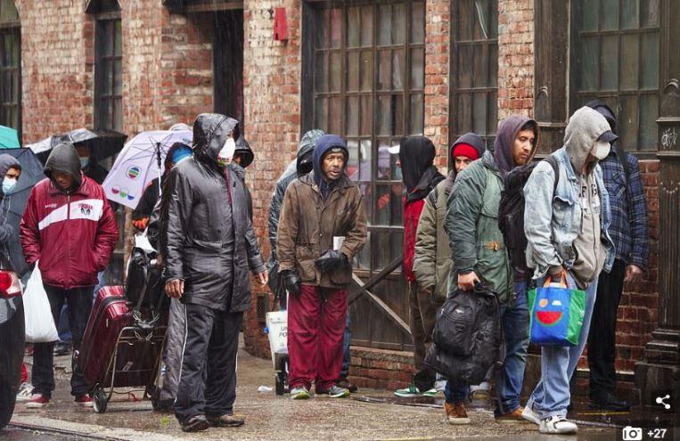 Conséquences flagrantes de leurs si Inadmissibles égoïsmes : 'Des centaines de personnes attendent de recevoir des repas à la Bowery Mission de New York, lundi. De longues files d'attente ont continué à se former devant les banques alimentaires et les bureaux de chômage dans des dizaines de villes au cours du week-end, alors que la pandémie de coronavirus touche durement les familles, laissant beaucoup d'entre elles dans l'incertitude quant à la date de leur prochain chèque de paie. »