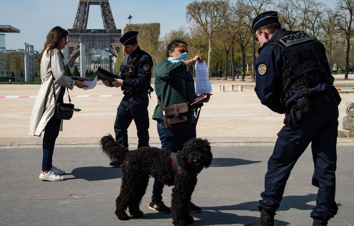 Des policiers contrôlent des passants près de la tour Eiffel à Paris, le 7 avril 2020. — AFP