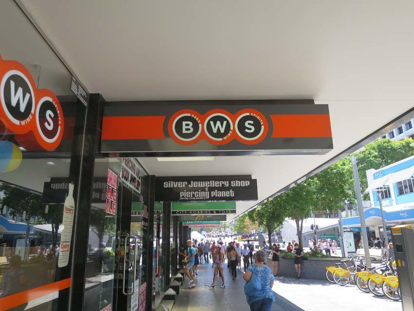 Sous les auvents, les publicités des magasins. Ici, le grand magasin BWS pour Bière, Wine, Spirits. Ph. Delahaye.