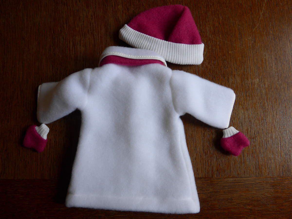 Le trousseau Corolle de Rose rose : un manteau doublé avec écharpe, bonnet et moufles ; une robe à bretelles et un petit pull blanc.