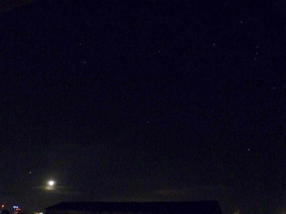 Photo du ciel au même moment : la Lune et Jupiter en bas à gauche de la photo, la constellation d'Orion en haut à droite de la photo.