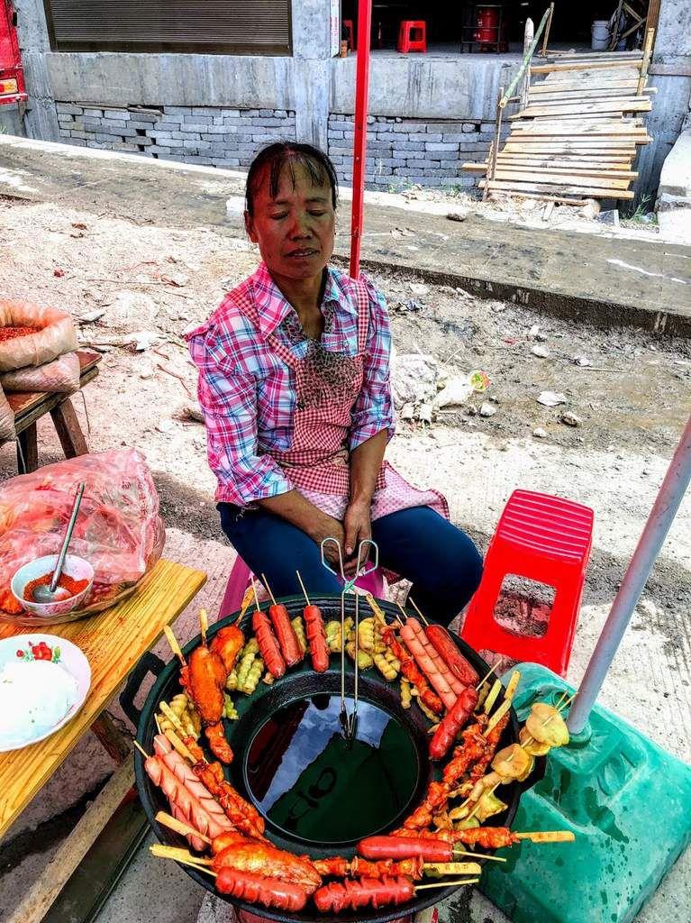 la cuisine de rue sur un marché de l'ethnie miao; les chinois  mangent peu chez eux surtout à midi; ces brochettes sont délicieuses et très peu chères;