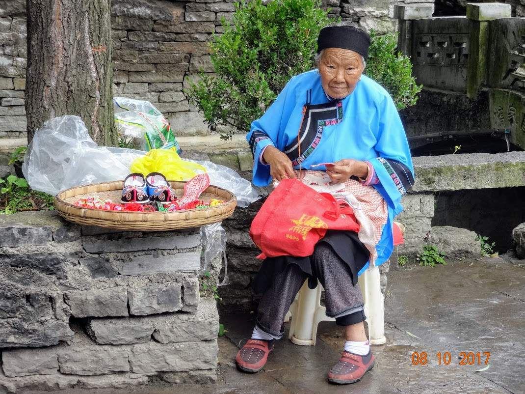 une femme han propose des objets artisanaux qu'elle a fabriqués dans un village touristique