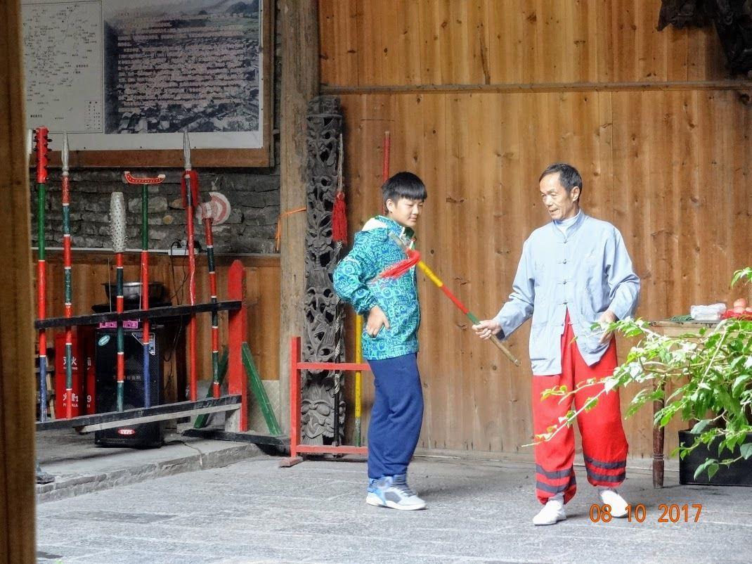 un ado s'initie à la danse du bâton dans un village touristique