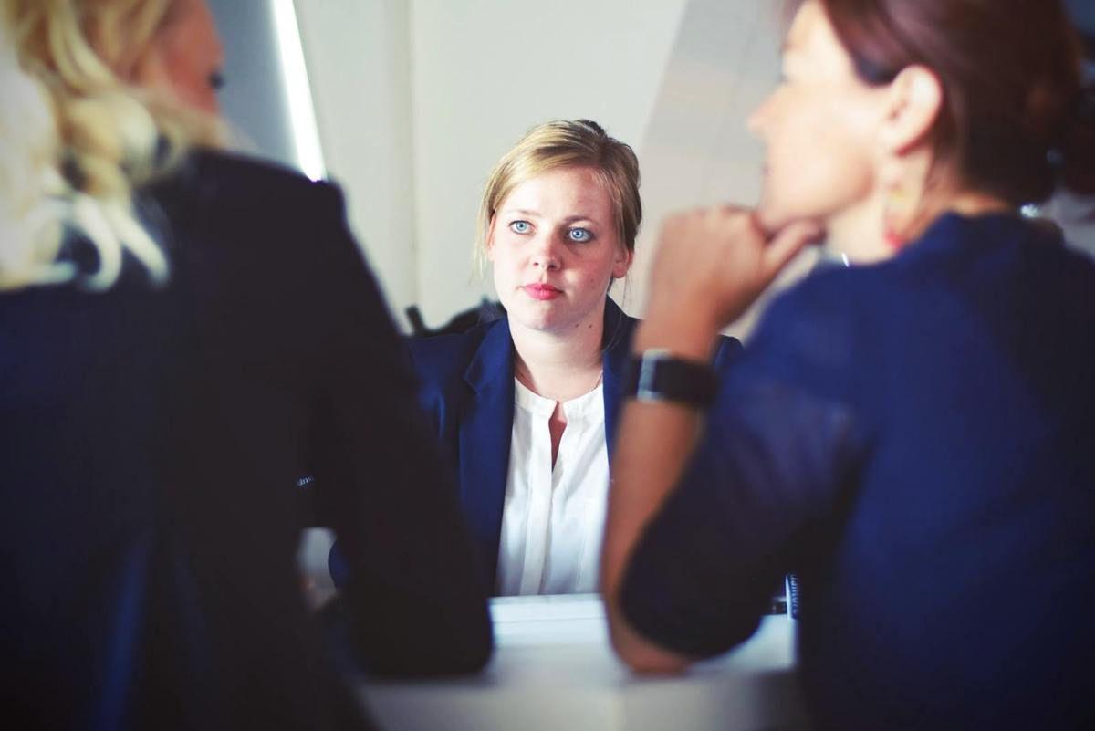 femme blonde qui passe un entretien d'embauche avec deux autres femmes de dos