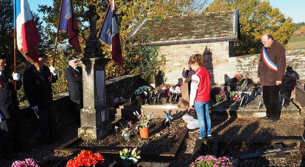 Une élève du Rassemblement Pédagogique Intercommunal La Chapelle aux Bois/Les Voivres dépose un drapeau sur la tombe du soldat Roulet Léon.