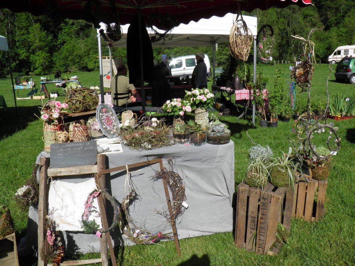 Un très beau stand d'objets décoratifs à base de fleurs séchées, de mousse, de branches et des joubarbes sempervirens présentées en pots de mousse.