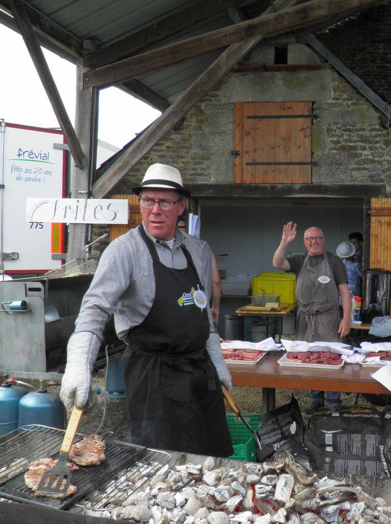 Joël est préposé à la cuisson de la viande, Michel au fond s'occupe des frites.