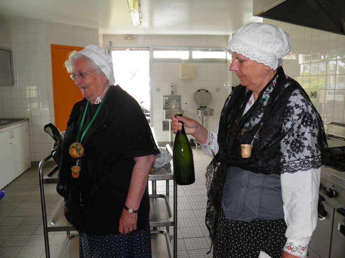 Christiane, le Grand Historiographe et Dominique, un des Prévosts, apportent les bouteilles à ouvrir.