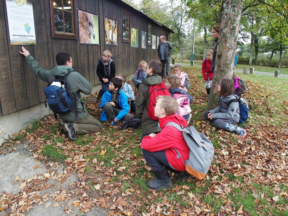 Les enfants observent l'exposition de photos et écoutent les explications de leur instituteur.