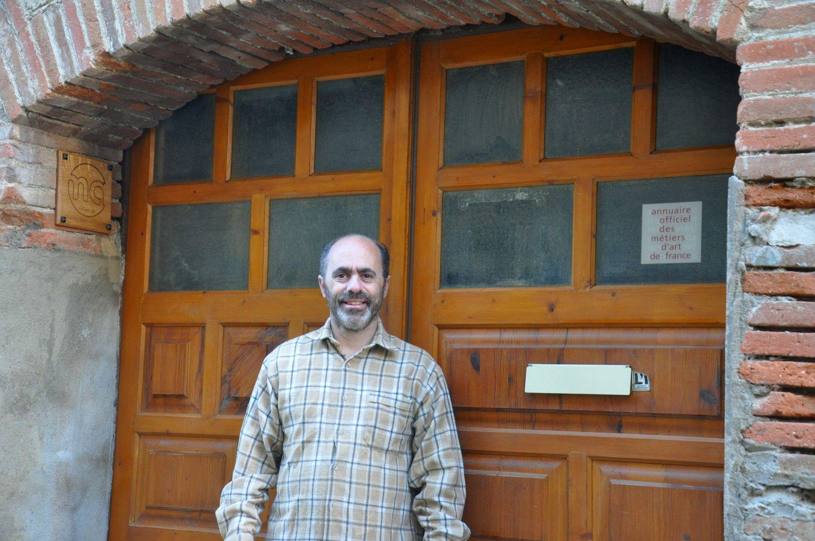Christian Séguié menuisier ébéniste devant la porte de son atelier.