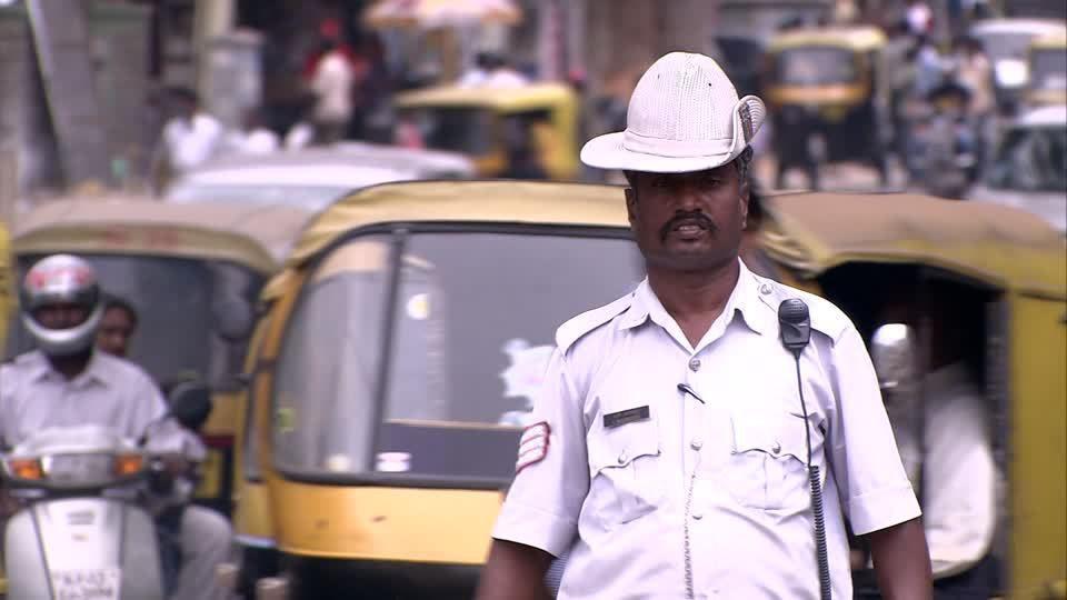 Un policier régule la circulation en Inde