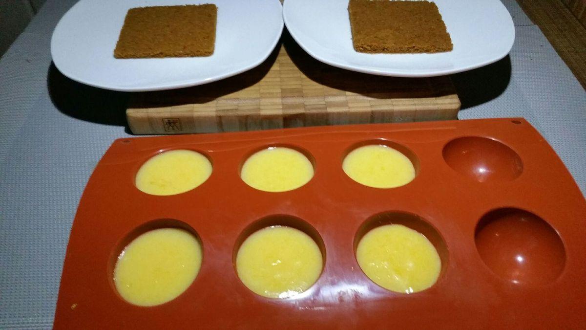 4 - Réaliser le dressage de vos tartes au citron en plaçant les rectangles de base sablée au spéculoos sur des assiette à dessert. Y déposer les demi-sphères au lemon curd.