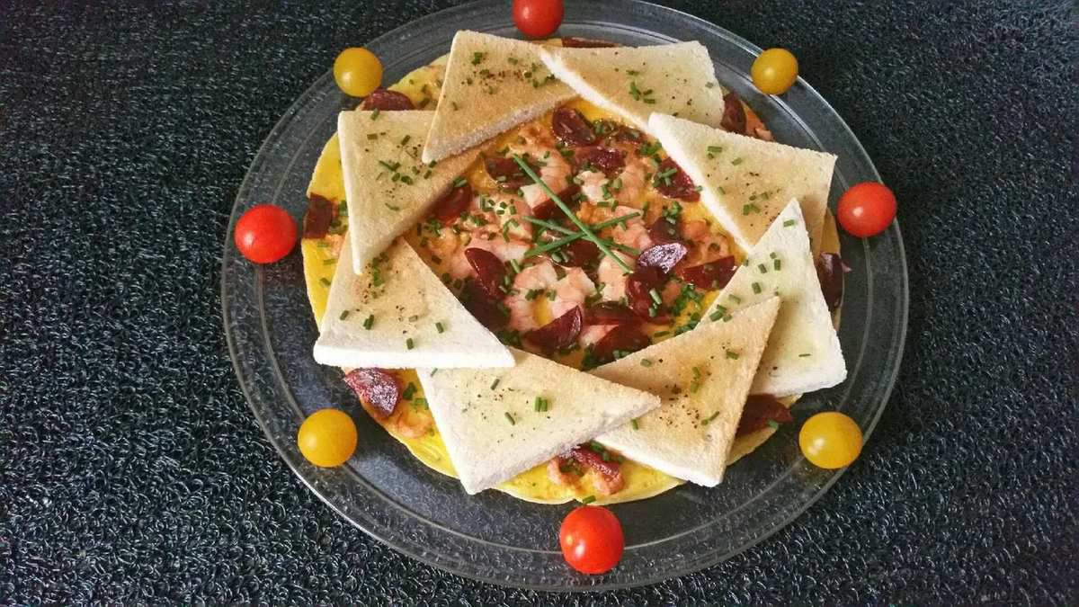 4 - Disposer votre omelette sur un plat de service et parsemer de ciboulette hachée, partager en portions accompagnées de tomates cerise et salade avec une petite vinaigrette.