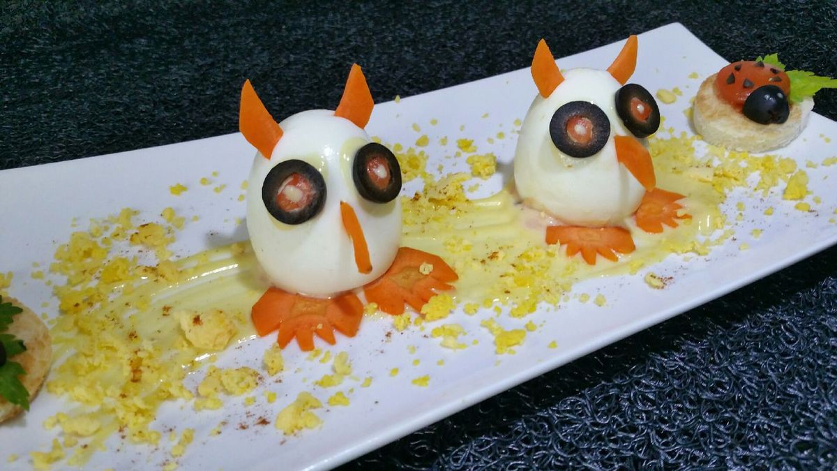 5 - Disposer les oeufs sur l'assiette de service. Les décorer avec les morceaux de carotte et olives pour matérialiser les pattes, le bec, les yeux et les oreilles du hibou. Parsemer de miettes de jaune d'oeuf. Placer à chaque extrémité de l'assiette les disques de pain de mie surmontés des ronds de tomates et de petits éclats, morceaux d'olives et brins de persil plat pour réaliser de petites coccinelles. Servir frais