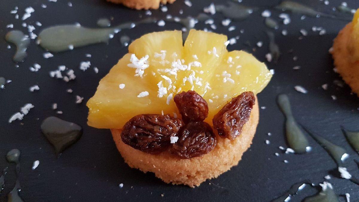 2 - Disposer les quartiers d'ananas sur les palets, compléter avec les raisins secs égouttés. Saupoudrer de noix de coco râpé. Servir accompagné de glace rhum raisins (ou autre parfum de votre choix).