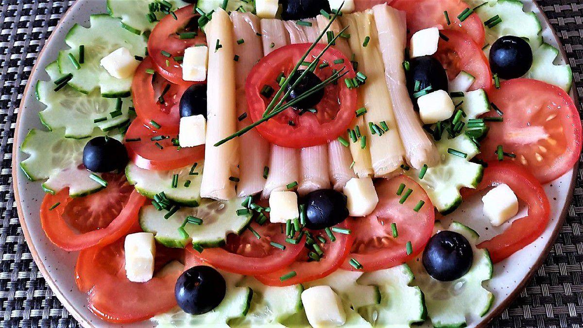 1 - Laver les tomates et les couper en rondelles. Laver et sécher le concombre (bio de préférence pour garder la peau), réaliser des encoches espacées sur la longueur du concombre à l'aide du crochet de côté d'un épluche patate. Découper le concombre en rondelles. Couper les olives noires en 2. Tailler l'emmental en cubes. Ciseler la ciboulette fraîche. Egoutter les blancs de poireaux cuits. Disposer joliment en les alternant les crudités sur une assiette de service, placer les blancs de poireau au centre, décorer avec les olives et les cubes d'emmental et parsemer de ciboulette ciselée. Déguster cette assiette de crudités accompagnée d'un vinaigrette légère.