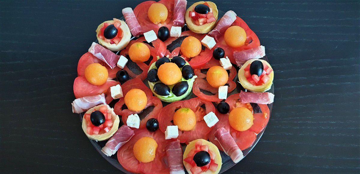 1 - Laver et sécher les tomates et le concombre. Couper la tomate (type coeur de boeuf) en rondelles, et la petite tomate (Roma ou autre) en dés. Réserver. Eplucher le 1/2 concombre (laisser la peau si concombre bio) et le tailler en spaghettis avec un outil spécial (en vente dans le commerce, magasins de cuisine, ou sur internet). Couper le melon en 2, ôter les pépins et prélever des billes à l'aide d'une cuillère parisienne. Réserver. Rouler les tranches de jambon rouge en forme de cigarettes russes et les couper en 2.  Tailler la feta en petits cubes. Egoutter les fonds d'artichauts et les remplir de petits dés de tomate. Disposer joliment vos éléments sur un plat de service en plaçant les spaghettis de concombre au centre, les rondelles de tomates autour en y intercalant le jambon roulé et les fonds d'artichauts. Décorer avec les billes de melon, les cubes de feta et les olives noires entières ou taillées en deux. Servir en entrée, accompagné d'une sauce vinaigrette de votre choix.