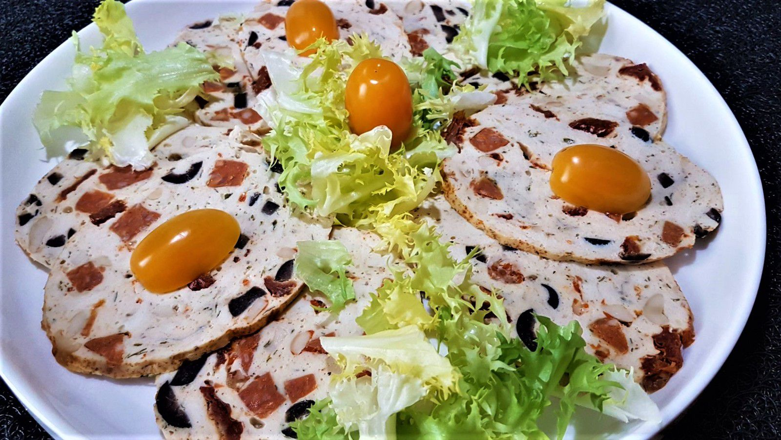 5 - Découper en tranches, disposer sur un plat de service en décorant avec un peu de salade frisée et quelques tomates cerises. Servir froid ou tiède accompagné d'une sauce au chorizo.