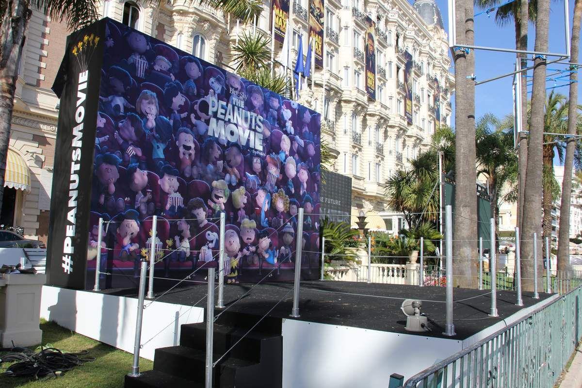 """Comme chaque année, l'InterContinental Carlton s'associe à de nombreux projets cinématographiques américains. D'un côté, écrans géants et affichages inédits pour """"Terminator Genisys"""", de l'autre galerie de personnages pour """"Mad Max : Fury Road"""". Au dernier étage, bannière exclusive pour """"Pixels"""" et podium pour """"Snoopy Et Les Peanuts"""" dans les jardins de l'hôtel. Les personnes du public seront d'ailleurs invitées à prendre la pose devant un photographe, aux côtés de Snoopy, Charlie Brown, Lucy, Linus, Schroeder, Sally, Peppermint Patty et Woodstock, confortablement installés dans des fauteuils de cinéma. Chacun pourra partager les clichés de son choix sur les réseaux sociaux et une version papier souvenir sera offerte."""